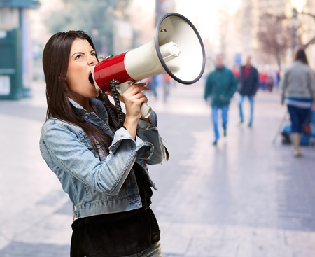 portrait of young woman screaming with megaphone at crowded street Stock Photo - 16252274