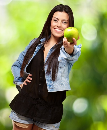 causal clothing: Woman Showing Green Apple, Outdoor Stock Photo