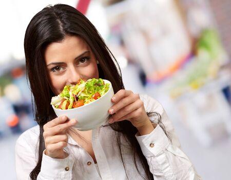 nice food: Портрет молодой женщины, держащей свежий салат в улице