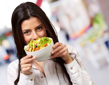 portrait of young woman holding a fresh salad at street
