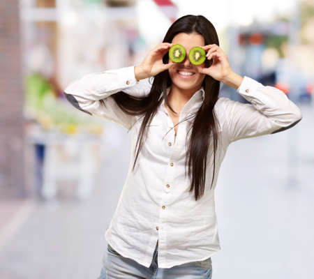 portrait of young girl holding kiwi slices in front of her eyes at street Stock Photo - 16252290