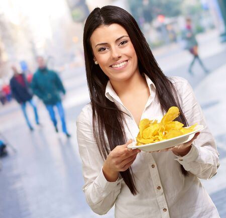 portrait of young woman holding a potato chips plate at city photo