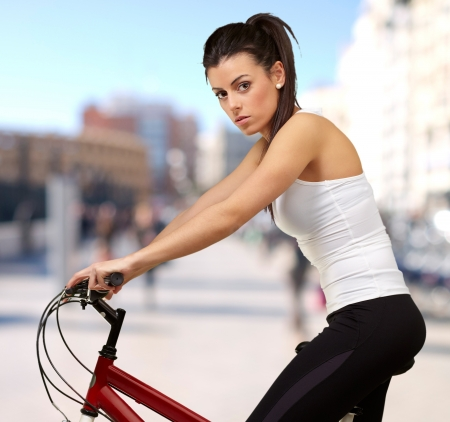 portrait of young woman cycling at city photo