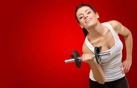 Young woman holding dumbells on red background photo