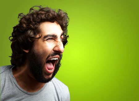agitated: Portrait Of A Man Shouting On Green Background