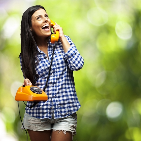 portrait of young woman talking on vintage telephone against a nature background Stock Photo - 16303990