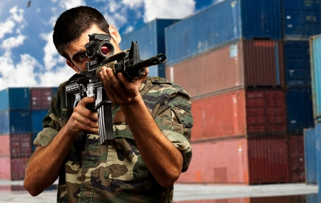 assault rifle: Soldier Gunman Aiming His Target against an industrial Background Stock Photo