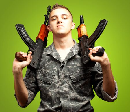 assault rifle: Portrait Of Soldier Holding Gun On green Background