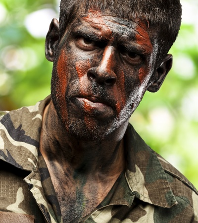 young soldier with camouflage paint looking very serious over at jungle photo