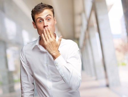 Portrait Of Young Man Covering His Mouth With Hand, Outdoor Stock Photo