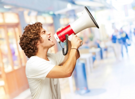 Portrait Of Young Man Shouting With A Megaphone, Indoor photo