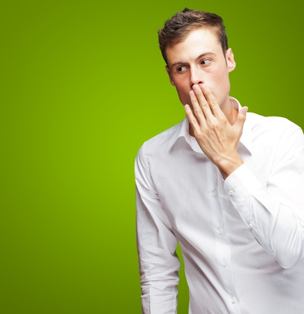 Portrait Of Young Man Covering His Mouth With Hand On Green Background Stock Photo - 16303920