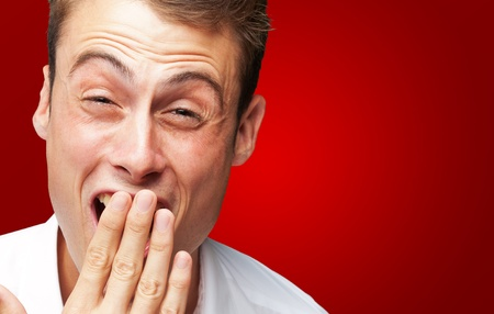 Portrait Of Young Man Covering His Mouth With Hand On Red Background Stock Photo - 16303914