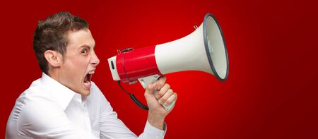 Portrait Of Young Man Shouting On Megaphone Isolated On Red Background photo