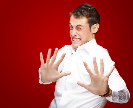 defenseless: A Young Man Holding His Hands Out In Fear On Red Background