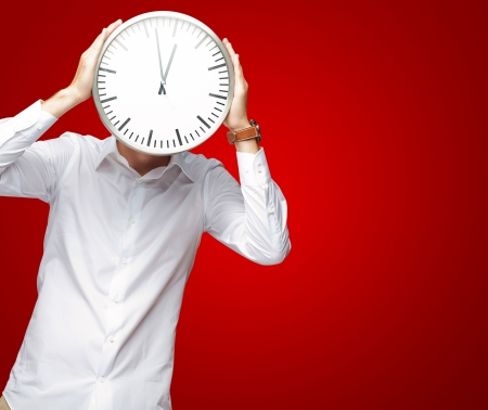 Young Man Holding Big Clock Covering His Face On Red Background photo