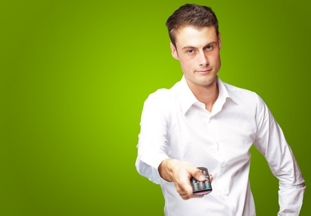 pointing device: Man Holding Remote In His Hand On Green Background