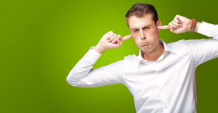 Portrait Of Young Man With Finger In His Ear On Green Background