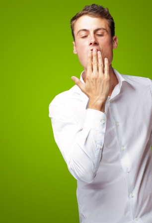 Portrait Of Young Man Yawning Isolated On Green Background photo