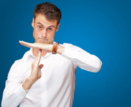Portrait Of Young Man Gesturing Time Out Sign On Blue Background