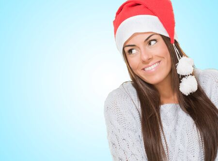 Happy christmas woman looking up against a blue background Stock Photo - 16303935