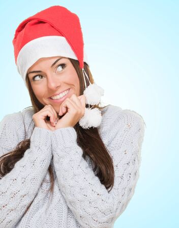 Woman wearing a christmas hat and thinking against a blue background Stock Photo - 16303940