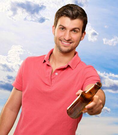 botellas vacias: hombre joven sosteniendo una cerveza, exterior