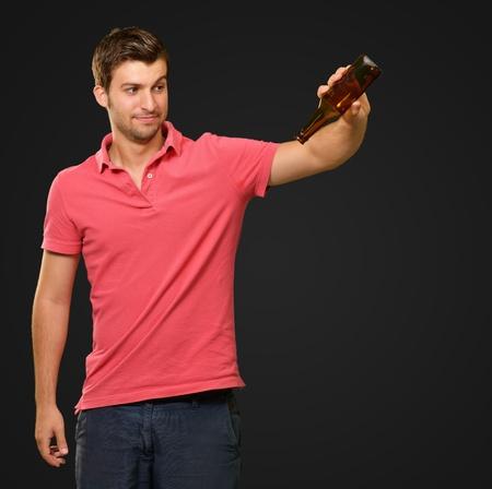 Portrait Of Young Man Holding Empty Bottle On Black Background photo