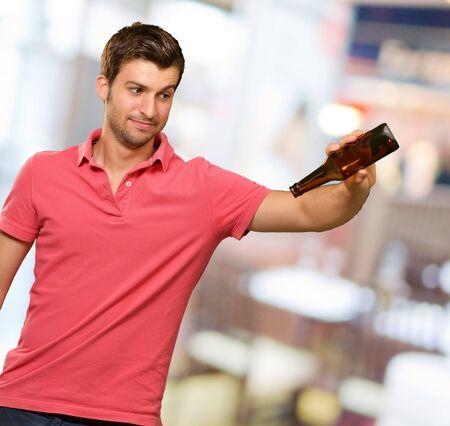 botellas vacias: Retrato de hombre joven sosteniendo la botella vacía, al aire libre