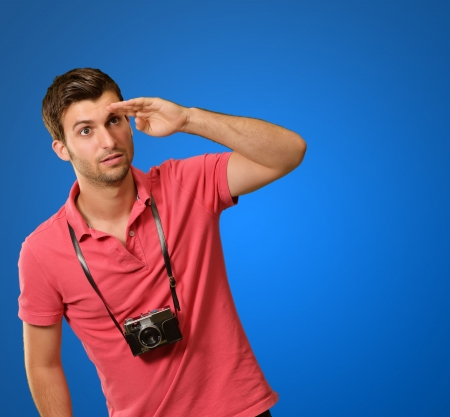 causal clothing: Portrait of a man looking for something on blue background