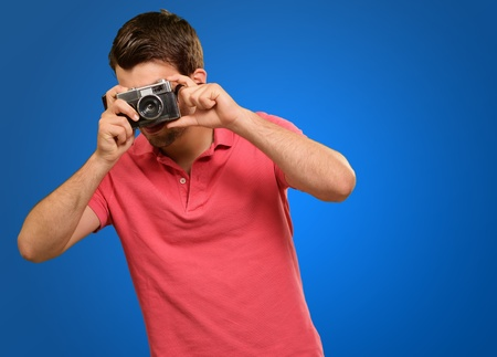 Portrait of a man taking photo on blue background photo