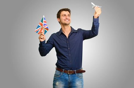 Man holding flag and miniature of airplane on grey background photo