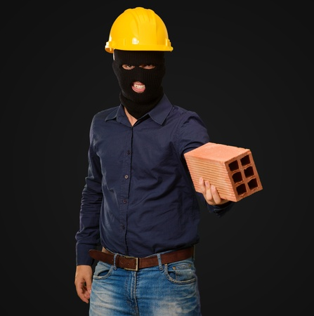 angry criminal man with brick isolated on black background Stock Photo - 16290919