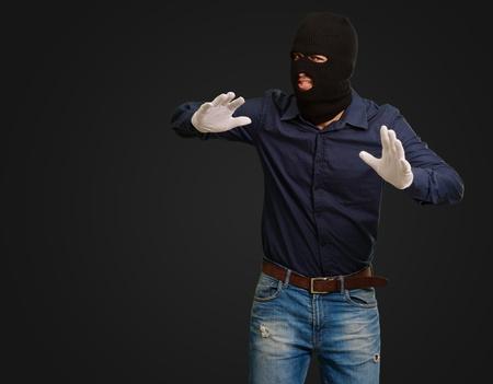 handglove: Burglar In Face Mask Isolated On Black Background