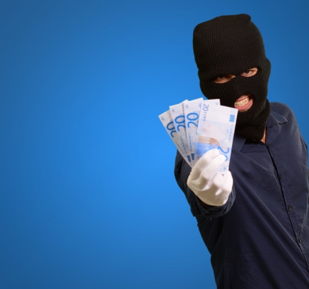 Burglar In Face Mask On Blue Background Stock Photo - 16288940