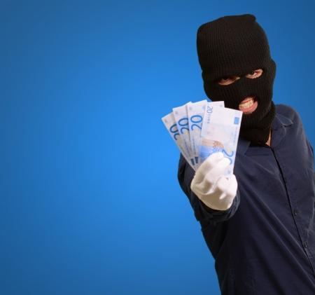 handglove: Burglar In Face Mask On Blue Background