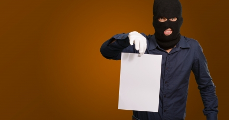 Burglar In Face Mask On Brown Background Stock Photo - 16290596