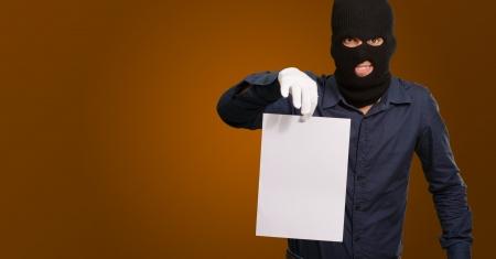 handglove: Burglar In Face Mask On Brown Background Stock Photo
