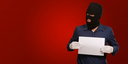 swindled: Man wearing a robber mask showing a blank paper on red background Stock Photo