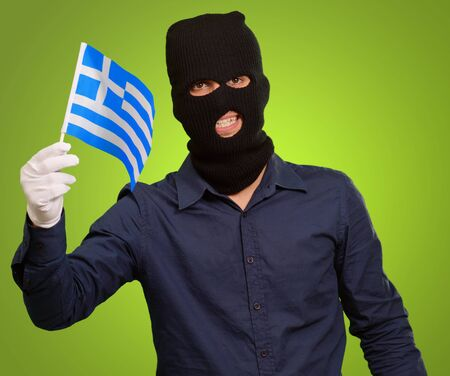 perpetrator: Man wearing robber mask and holding flag on green background Stock Photo