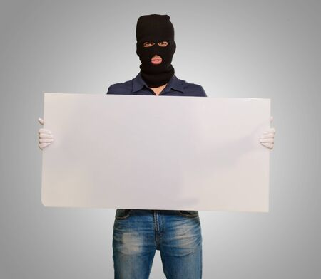 thievery: Man wearing mask holding a blank card isolated on gray background
