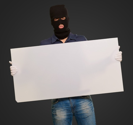 Man wearing mask holding a blank card isolated on black background photo
