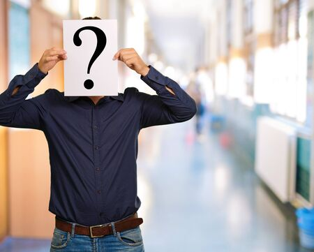 interrogative: El hombre de pie con un signo de interrogaci�n tablero, al aire libre Foto de archivo
