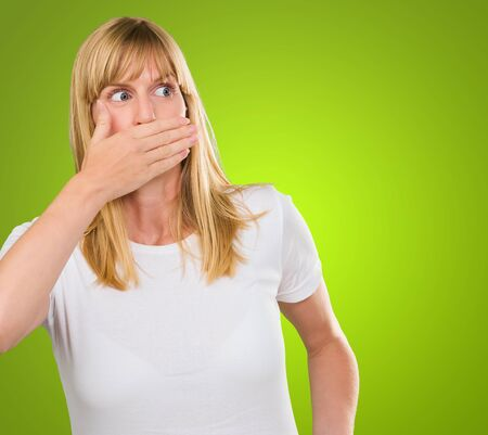 Young Woman With Hand On Mouth against a green background Stock Photo - 16290536