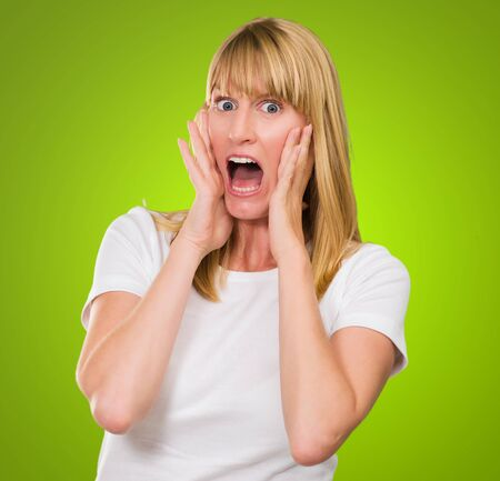 Portrait Of Shocked Woman against a green background Stock Photo - 16290085