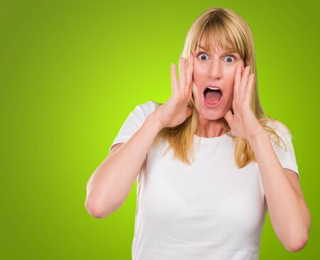 Portrait Of Shocked Woman against a green background Stock Photo - 16290463