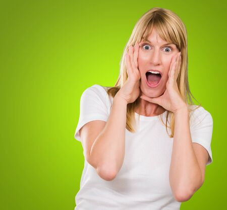 Portrait Of Shocked Woman against a green background Stock Photo - 16290252