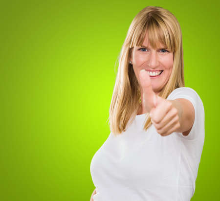 Happy Woman Showing Thumb Up against a green background Stock Photo - 16290353