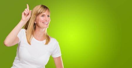 Women Pointing Up With Hand On Hip against a green background Stock Photo - 16290688