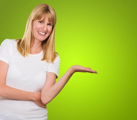 Happy Woman Presenting against a green background Stock Photo - 16290929